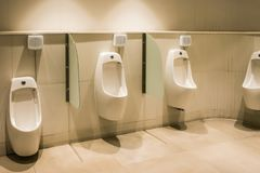 Линия белых писсуаров фарфора в чистых, светлых общественных туалетах Стоковое Изображение RF