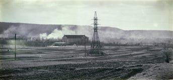 Линия высокого напряжения пропуская через поле на заднем плане холмов в дыме Черно-белое фото в ретро стиле Стоковое фото RF
