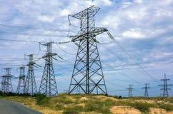 Линия высокого напряжения с электрическими опорами на предпосылке clou Стоковая Фотография RF
