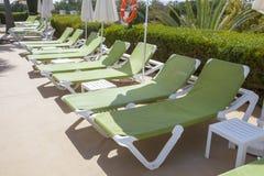 Линия зеленых sunloungers на бассейне Стоковая Фотография