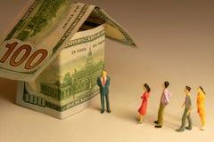 Линия или очередь ожидания на фронте дома сделали из 100 долларовых банкнот Расходы недвижимости строя ипотеку и свойство стоковое фото rf