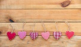 Линия красных сердец ткани вися, старая деревянная предпосылка Стоковое Изображение