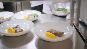 Линия крупного плана блюд плит Шеф-повара группы занятые в коммерчески кухне точного обедая ресторана Штат в ресторане видеоматериал