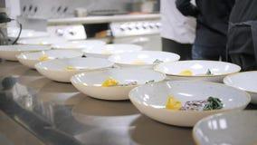 Линия крупного плана блюд плит Шеф-повара группы занятые в коммерчески кухне точного обедая ресторана Штат в ресторане акции видеоматериалы