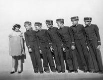 Линия молодых bellhops усмехаясь на девушке стоковое изображение