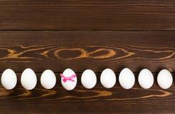 Линия пасхальных яя на деревянной предпосылке Одно из яичек имеет розовый смычок Стоковые Фотографии RF