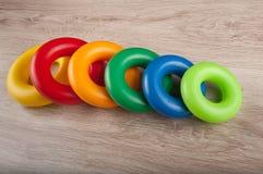 Линия покрашенных колец игрушки пластичных на таблице Стоковые Изображения RF