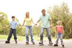 линия семьи носить коньков парка стоковая фотография