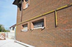 Линия соединение трубы газа системы установленное в экстерьер стены дома Наладьте связи газопровода от стали или медных труб Стоковые Фото