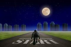 Линия СТАРТА бизнесмена перед городом Взгляд ночи задний Eleme стоковые изображения