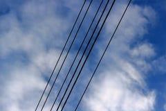 Линия электропередачи против предпосылки пасмурного голубого неба стоковая фотография
