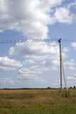 Линия электропередач под голубым небом с облаками белизны Стоковые Фото