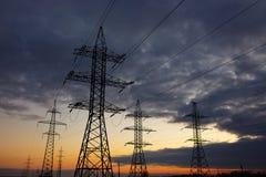Линия электропередач подшипника металла высоковольтная на заходе солнца Стоковое фото RF