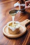 Липкий сыр бри на деревянной доске служил с зеленым салатом дуба и свежим испеченным отрезанным хлебом стоковое изображение rf