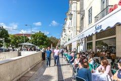 Лиссабон, Португалия - 9-ое мая 2018 - туристы и locals идя в традиционную тропу в Лиссабоне к центру города, рестораны и деревья стоковая фотография