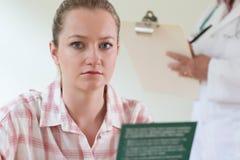 Листовка чтения молодой женщины в Doctor& x27; хирургия s Стоковое Фото