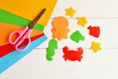 Листы покрашенной бумаги, ножниц, клея, бумажных рыб и тварей моря принципиальная схема diy Легкая идея ремесла детей Бумажное ре Стоковое Изображение