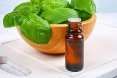 Листья базилика и малой бутылки масла на конкретной таблице Стоковое фото RF
