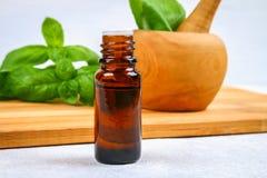 Листья базилика и малой бутылки масла на конкретной таблице Стоковые Изображения RF