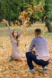 Листья девушки бросая в парке Стоковые Фотографии RF