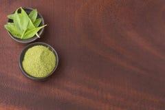 Листья зеленого цвета и порошок Стевии - rebaudiana Стевии Взгляд сверху стоковая фотография