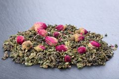 Листья зеленого чая с розовыми бутонами стоковая фотография