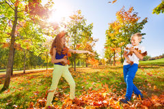 Листья игры девушки и мальчика бросая в лесе Стоковое фото RF