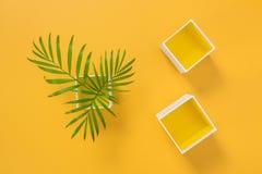 Листья ладони и декоративные коробки на желтой предпосылке стоковое фото rf