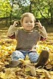 листья мальчика сидя желтый цвет стоковые изображения rf