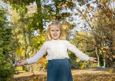 Листья осени девушки бросая в парке Стоковые Изображения RF