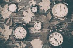 Листья осени и будильники на деревянном столе Стоковые Изображения RF