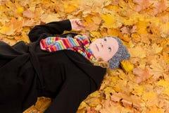 Листья осени молодой женщины daydreaming Стоковое фото RF