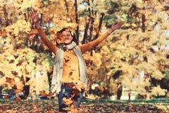 Листья осени падая на счастливую молодую женщину стоковое фото