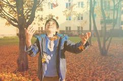 Листья осени счастливого мальчика бросая стоковая фотография rf