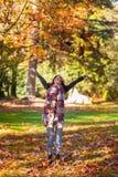 Листья падения молодой женщины брюнета бросая в воздух стоковая фотография rf