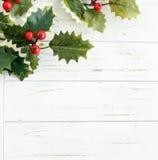 Листья падуба на белой деревянной предпосылке Стоковая Фотография