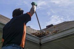 Листья работника подметая от долины крыши стоковое фото rf