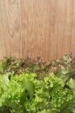 Листья салата на разделочной доске Стоковые Фотографии RF