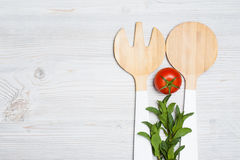 Листья томата и мяты с деревянным столовым прибором на белой деревянной предпосылке Стоковое Изображение
