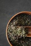 Листья чая на деревянном шаре на темной каменной вертикали предпосылки Стоковые Фото