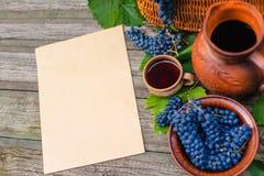 Лист бумаги для текста кладет около корзины, шара с виноградинами, опарника и чашки с вином на деревенскую древесину Предпосылка  Стоковое Изображение