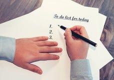 Лист бумаги перед человеком с словами: Сделать список для сегодня Планирование дел на день против как крюка hang долларов принцип Стоковое Изображение RF