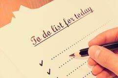 Лист бумаги перед человеком с словами: Сделать список для сегодня Планирование дел на день против как крюка hang долларов принцип Стоковые Фотографии RF