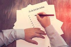 Лист бумаги перед человеком с словами: Сделать список для сегодня Планирование дел на день против как крюка hang долларов принцип Стоковое фото RF