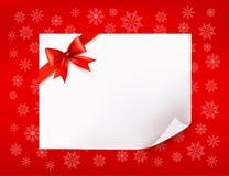 Лист бумаги рождества и красный смычок Стоковое Изображение
