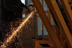 Лист инструментального металла работника меля с машиной и искрами точильщика стоковое изображение