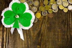 Лист клевера и много монетки на деревянной предпосылке Скопируйте затир Стоковое фото RF