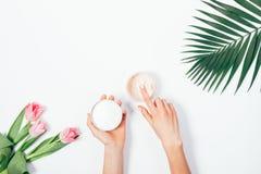 Лист ладони, букет розовых тюльпанов и косметическая сливк Стоковые Фотографии RF