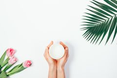 Лист ладони, букет розовых тюльпанов и опарник косметической сливк Стоковые Фото