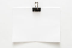 Лист чистого листа бумаги прикрепленный при зажим изолированный на белой предпосылке стоковая фотография